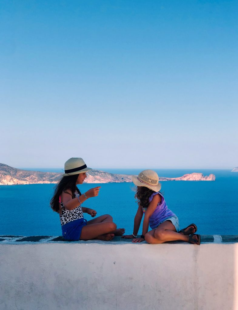 2 women sitting on white concrete bench near body of water during daytime